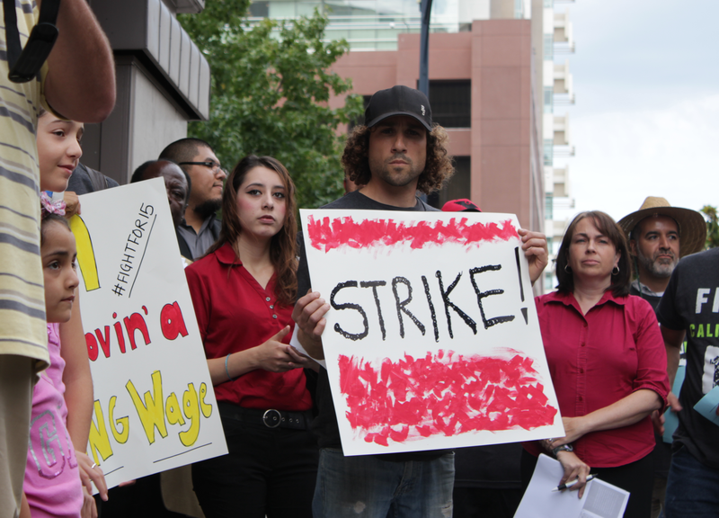 Debra Flores, an employee at Wendy's in downtown San Diego, stands amid prote...