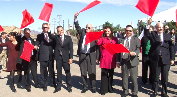 U.S. and Mexico officials wave flags to signal the beginning of construction ...
