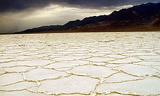 Badwater storm. Surreal patterns of salt with a stormy backdrop. Death Valley is famous for striking views, colorful geologic formations, and scenic vistas.