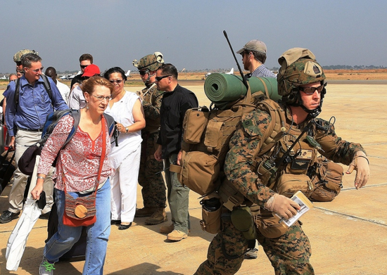 Marines guide U.S. citizens down the flight line in Juba, South Sudan, during an evacuation of personnel from the U.S. Embassy, on Jan. 3, 2014.