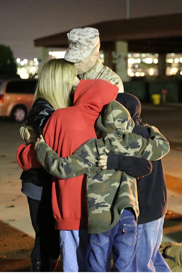 A Marine with I Marine Expeditionary Force (Forward) hugs his family as he wa...