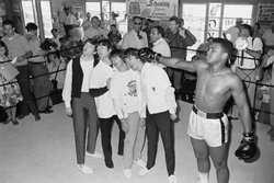 Boxer Cassius Clay, later known as Muhammad Ali, playfully hits The Beatles w...