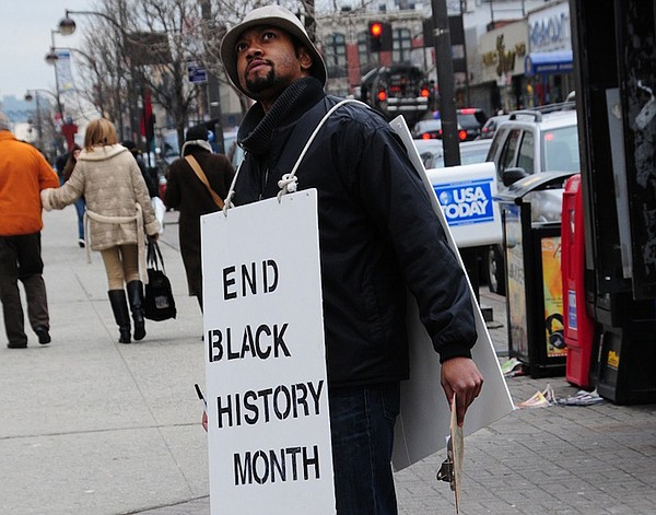 Filmmaker Shukree Tilghman wearing protest sign that reads