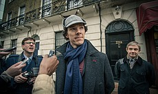 Benedict Cumberbatch as Sherlock Holmes. Holmes is surrounded by press with J...
