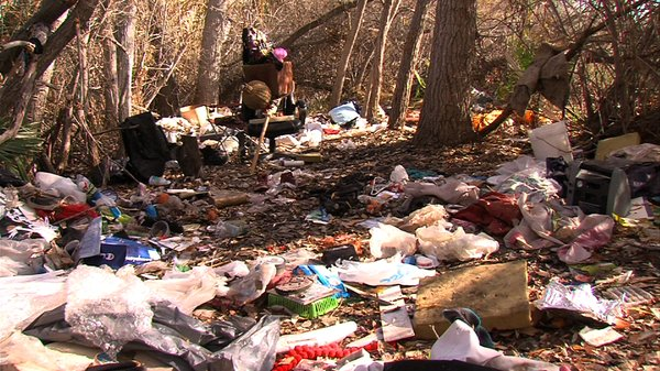 An abandoned homeless encampment litters the San Diego Ri...