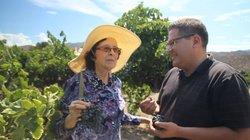 Doña Lupe shows host Jorge Meraz her vineyard and selection of delicious jams.