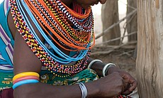 Young Samburu woman beading a necklace strand in Umoja Uaso Village, Kenya, 2000s.