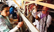 Amina Yabis, founder of the Women's Button Cooperative of Sefrou, weaving at the loom with cooperative member Khadija La Adraoui, Morocco, 2010.