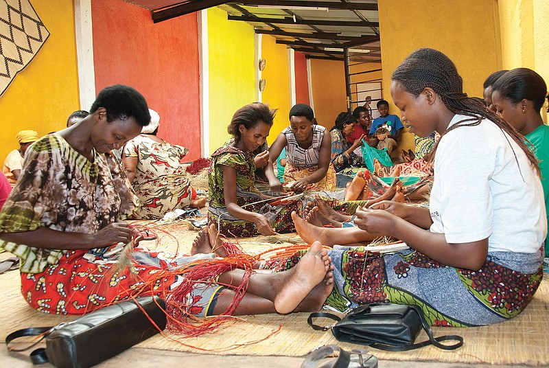 Members of the Gahaya Links Cooperative at their Kigali workshop weaving bask...