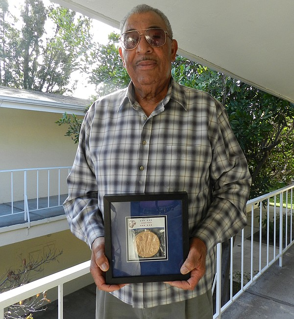 Dr. Reavis holding his Congressional Gold Medal awarded in 2012 for his servi...