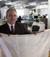 "KPBS General Manager Tom Karlo holds up a piece of fabric Christo and Jeanne-Claude's ""Running Fence"" that was installed in northern California in 1976."