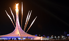 Fireworks explode behind the Olympic flame cauldron, announcing the official opening of the Sochi Winter Olympics.