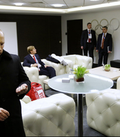 Russian President Vladimir Putin waits in the presidential lounge to be introduced at the opening ceremony of the Sochi 2014 Winter Olympics as a television screen displays snowflakes transforming into four Olympic rings, with one failing to form.