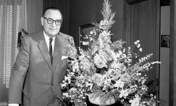 Gov. Pat Brown poses next to a bouquet.