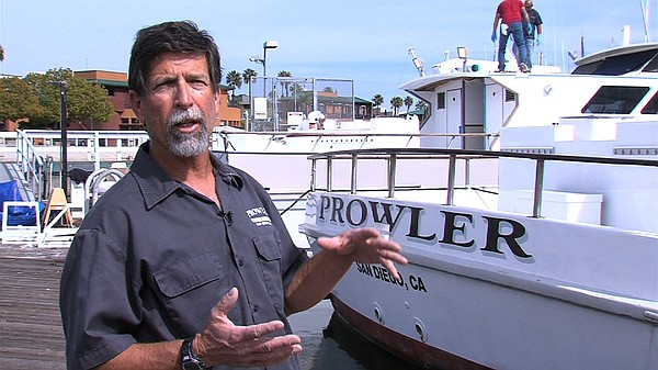 Buzz Brizendine stands in front of his boat, the Prowler.