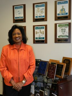 2014 Women's History Month Local Hero, Vickie Turner, standing next to several of the awards she has received through out the years.