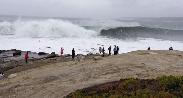 People stand on the rocky cliffs along Coast Blvd. in La Jolla to watch huge waves crash against the shore, March 1, 2014.