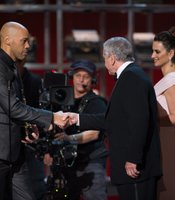 "John Ridley accepts his Oscar for Best Adapted Screenplay (for ""12 Years a Slave"") from Penelope Cruz and Robert DeNiro."
