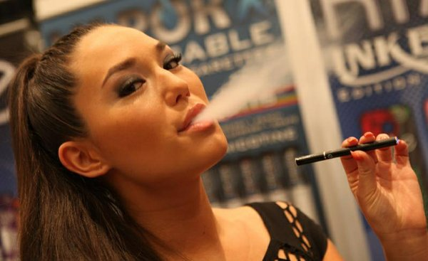 A woman exhales nicotine vapor from an e-cigarette in this undated photo.