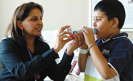 A woman shows a child with asthma how to use an inhaler.