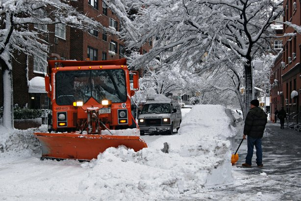 A snowplow clears a path down a tree-lined street through the snow in this un...