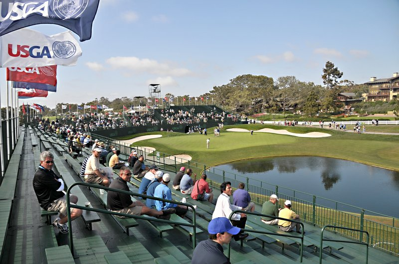 People sit in the stands at the 18th hole of the U.S. Open Championship at To...