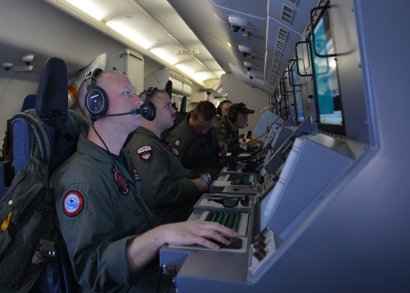 Crew members aboard a P-8A Poseidon search for Malaysia Airlines flight MH370.