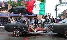 People line Avendia Revolucion for the Nov. 20 Parade as a trailer made from the back-half on an old Chevy Mustang is towed behind a vehicle.