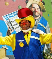 Colorful newspaper street vendor 'Pepe Nacho' spreads in arms in front of a mural of himself selling newspapers in his clown costume.