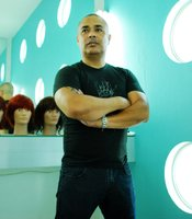 Hair stylist Charly stands in front of display wigs in Tijuana's 'Zero Salon.'
