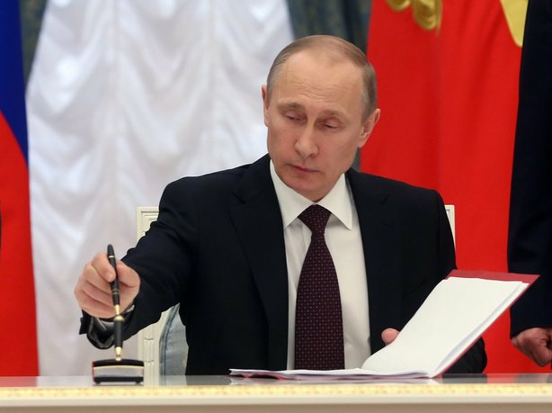On Friday in Moscow Russian President Vladimir Putin signs a bill making Crimea and the city of Sevastopol part of Russia.