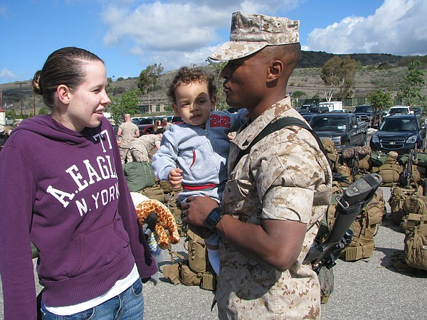 Cpl. Jason Singleton with his wife and son, before deploying from Camp Pendle...