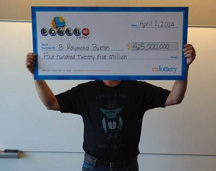 "This photo provided by the California Lottery shows Powerball winner B. Raymond Buxton holding a check for $425 million on April 1, 2014, in Sacramento, Calif. Buxton was wearing a shirt that featured a picture of Yoda and read, ""Luck of the Jedi I have."""
