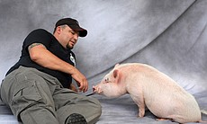 Dr. Len Lucero and Chris P. Bacon the pig playi...