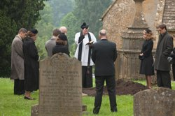 Reveal Father Brown (Mark Williams) reciting a prayer for the funeral of Moni...