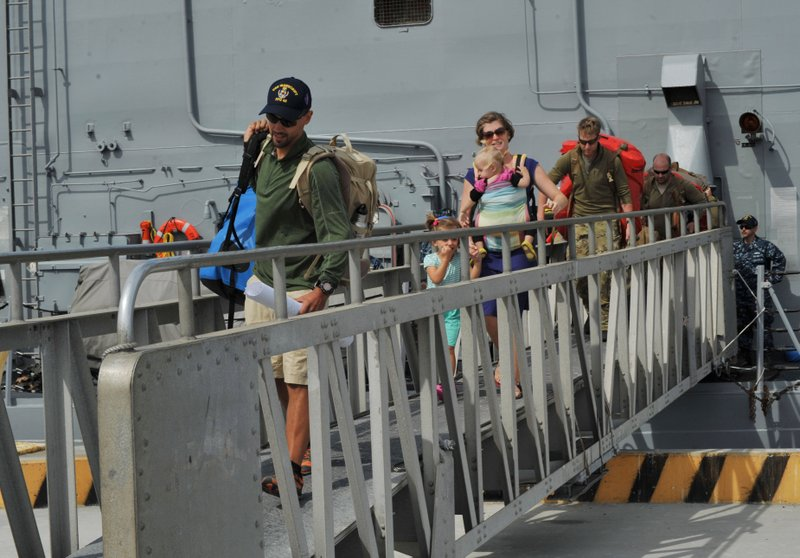 Eric and Charlotte Kaufman disembark from the USS Vandegrift with their two c...
