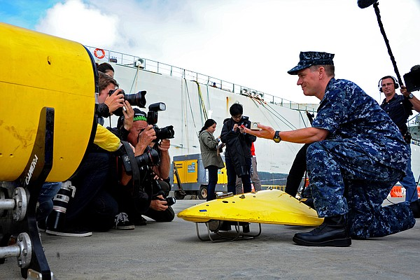 U.S. Navy Capt. Mark Matthews demonstrates a pinger locator for reporters in ...