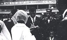 Muhammad Ali signing autographs at NOI Convention.