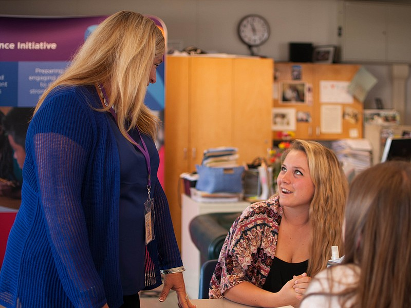 AP English and composition teacher Elizabeth Ward talks to some of her students.