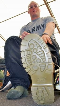 Army recruit examines his shoes.
