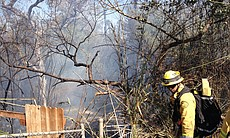 A firefighter on the scene of a brush fire in Santee that broke out in the afternoon of April 29, 2014.