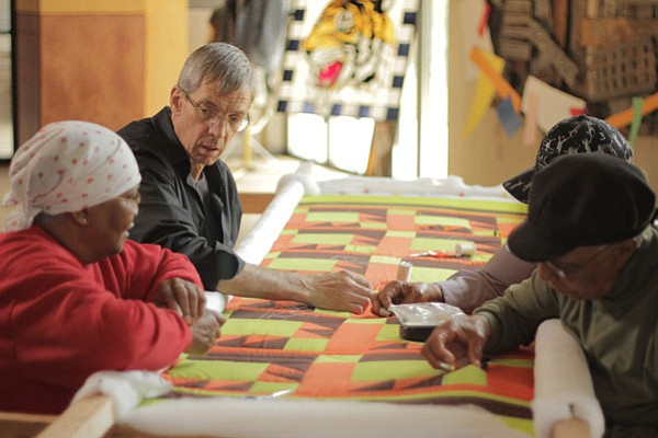 Quiltmaker Joe Cunningham at the frame with Gee's Bend quilters Ritamae Pettw...