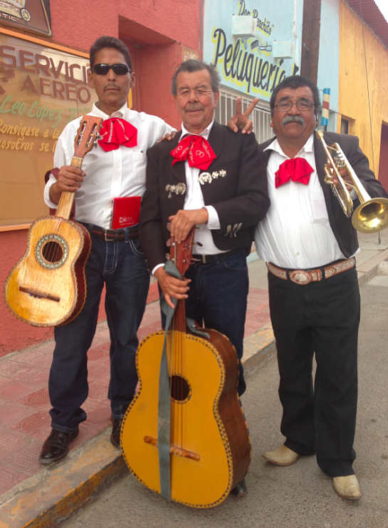 Three members of Mariachi Frontera pose after rehearsing in front of a neighb...