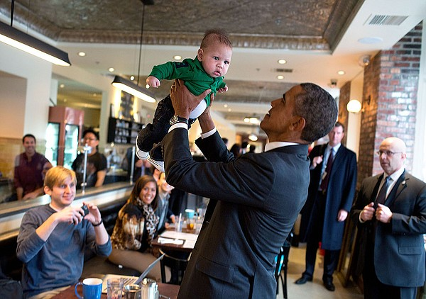 President Barack Obama lifts a baby while greeting patron...