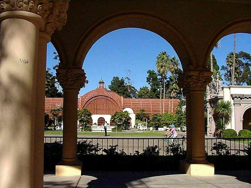 The Botanical Building is seen between columns of a walkway at Balboa Park in...