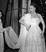 American-born dancer and jazz singer Josephine Baker (1906 - 1975) smiles at a woman holding the shawl to her gown backstage at a performance, Los Angeles, California, July 1951. (Agency reference - 3232806)