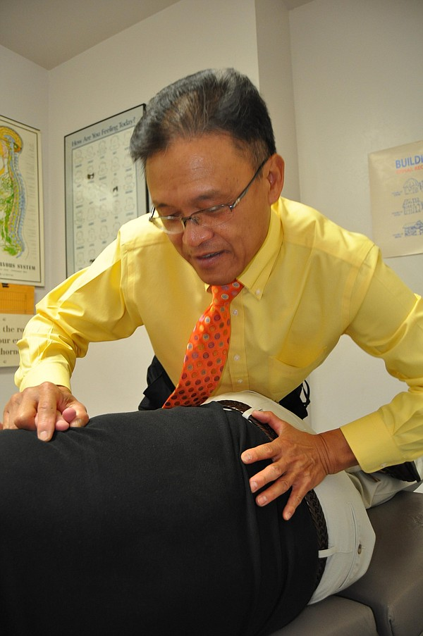 Dr. Chan working on a patient at his chiropractic office.