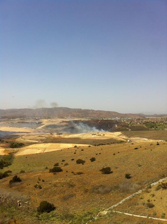 As seen from Carmel Valley Road, smoke billows into the a...