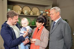 Mike Pruddy (Felix Scott) the nanny holds baby Ellingham, with Louisa and Mar...