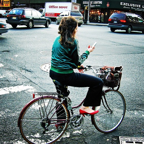 A woman stops in the street to use her phone while riding a bike.
